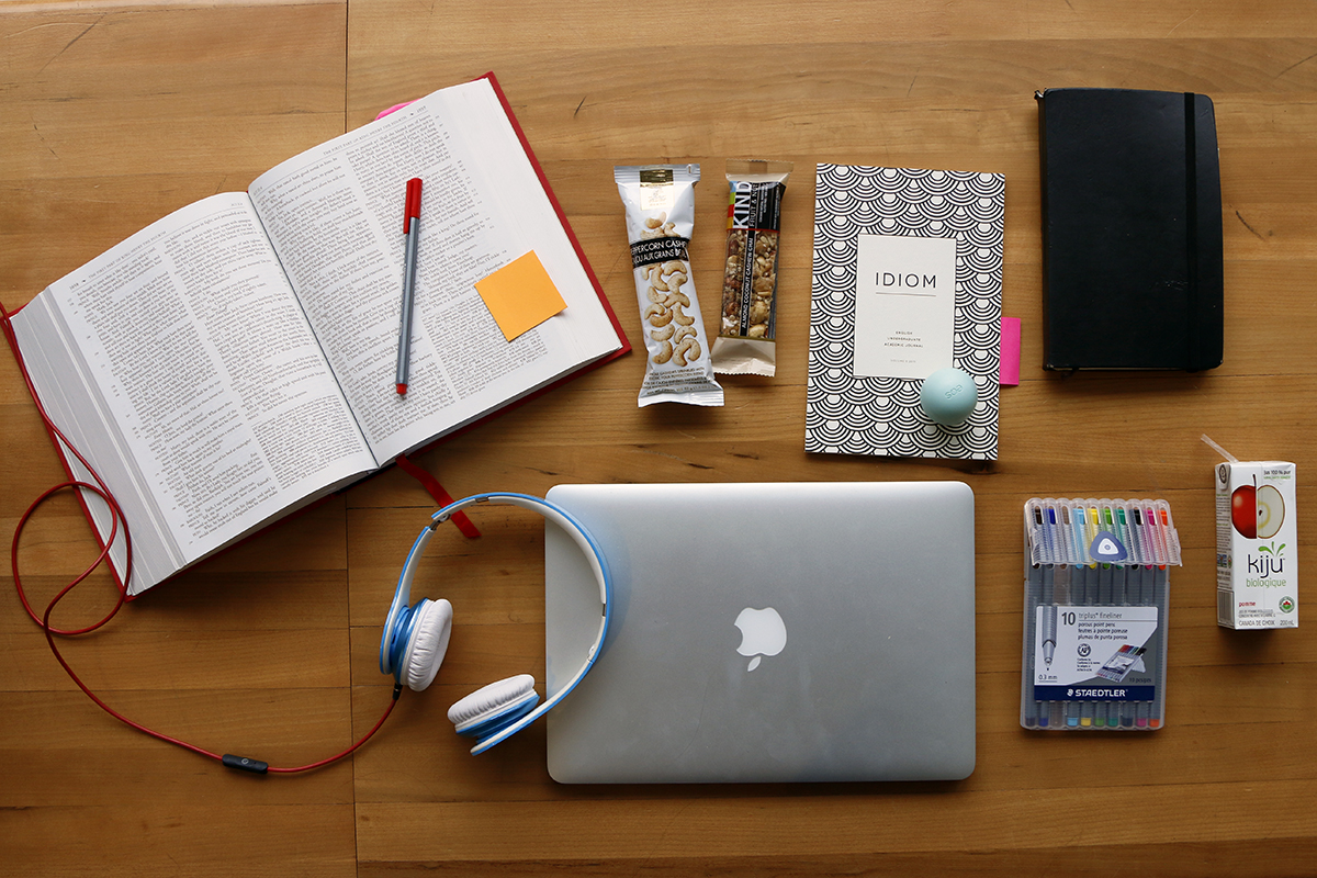 flatly arrangement of laptop, headphone, notebook and pen