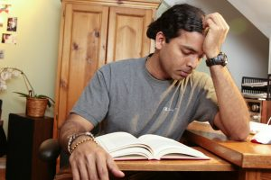 Photo of South Asian male student looks stressed by his desk at home