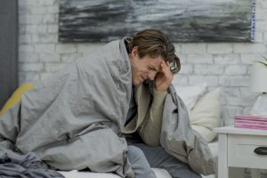 A young caucasian man is in bed on a sick day. He is holding his head, in pain.