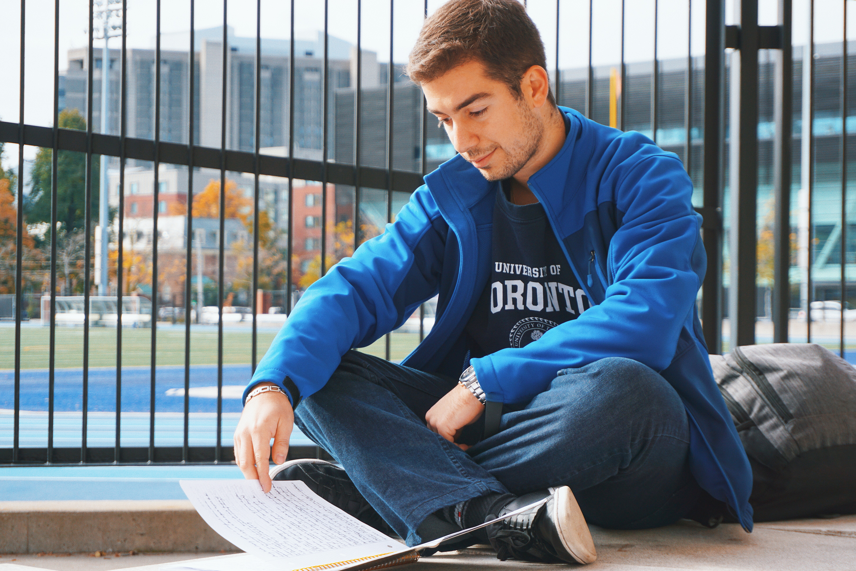 Photo of a male student studying outside Varsity Stadium