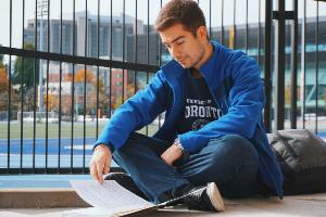 Photo of a student studying outside Varsity Stadium